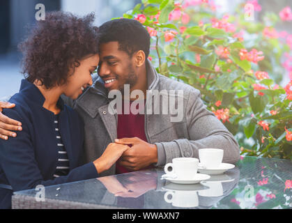 Sweet african couple holding each other hands in cafe - Stock Photo