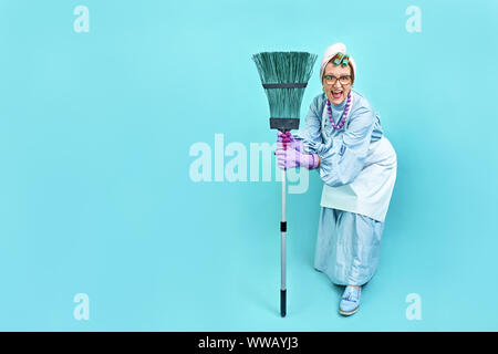 Cleaning Lady Fun. Elderly funny housewife fooling around with a broom. Full body. isolated. Comical cleaning lady, old woman funky - Stock Photo