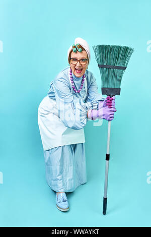 Cleaning Lady Fun. Elderly funny housewife fooling around with a broom. Full body blue isolated. Comical cleaning lady, old woman funky - Stock Photo