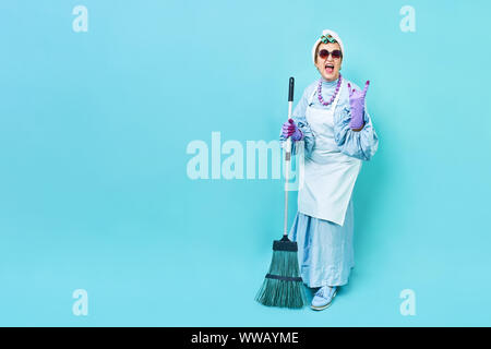 Cleaning Lady Fun. Elderly funky housewife fooling around with a broom. Full body isolated. Comical cleaning lady, old woman funky - Stock Photo