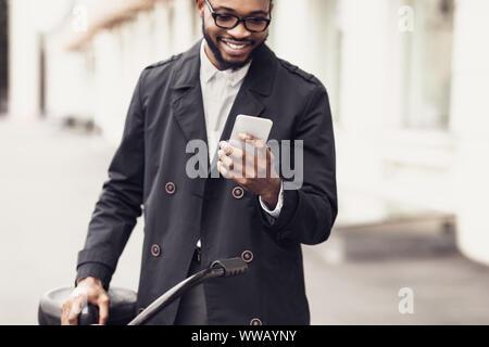 Young stylish man texting on phone standing near bike