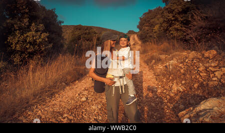 Happy traveler family, active young mother with cute little son on hands walking along mountainous road, enjoying summer camping in the mountains - Stock Photo