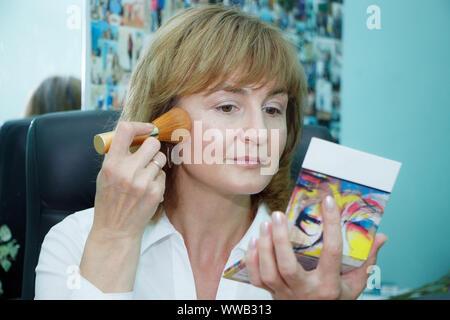 Close up of a mature blonde woman doing face makeup, selective focus