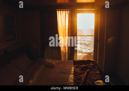 Sunset over the sea seen from inside the cabin of a cruise ship, Italy - Stock Photo