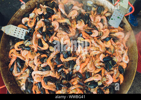 Paella seafood is cooked in a large capacity. Large - Stock Photo