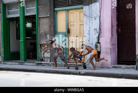 Boys race on a cart down the street in Havana, Cuba - Stock Photo