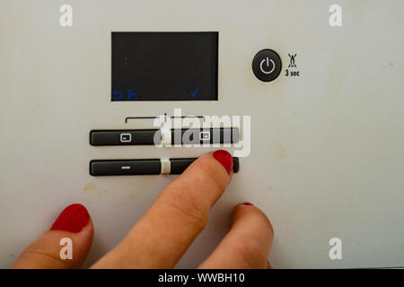 Woman hand try to turn off and on the central heating in the room. Female hands on the central heating control panel. Girl hand setting temperature to - Stock Photo