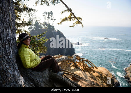 A woman looks out at the rugged sea stacks along the Oregon Coast trail in the Samuel H Boardman scenic coastal corridor near Secret Beach. - Stock Photo