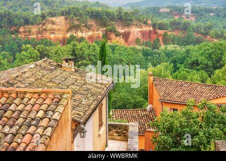 In Roussillon, France, houses made from colorful, locally mined ochre, with the former quarry in the background, as forest returns to the closed mine. - Stock Photo