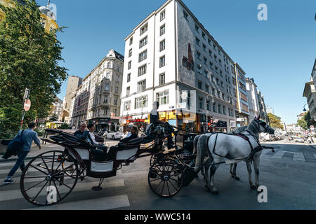People sitting in open carriage during city tour in the city center of Vienna - capital and largest Austrian city. - Stock Photo