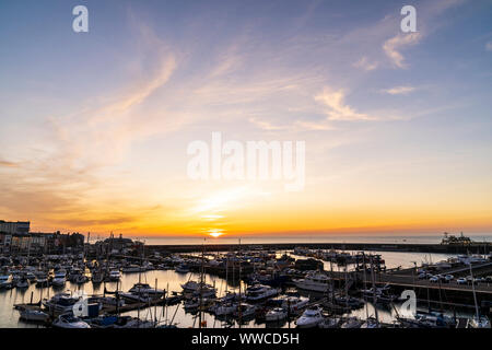Sunrise over the English Channel and the harbour at the coastal town of Ramsgate on the Kent coast in England. Harbour and yachting marina with a thin band off orange yellow on the horizon with the sun rising from the sea, blue sky with wispy clouds above. - Stock Photo