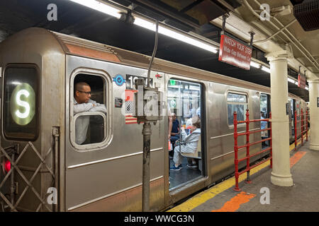 A conductor awaits the departure on the S train, the subway shuttle from Times Square to Grand Central Station. In Manhattan, New York City. - Stock Photo