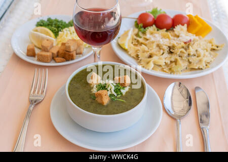 Green cream soup from spinach with croutons, cheese and fresh parsley in white bowl, close up - Stock Photo