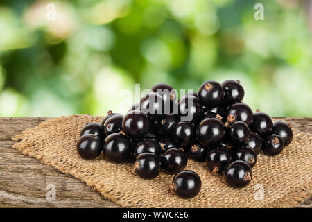 Black currants on burlap and wooden background. - Stock Photo