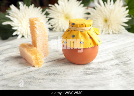 Honeycombs and ceramic Pot of honey and white flowers at the wooden table - Stock Photo