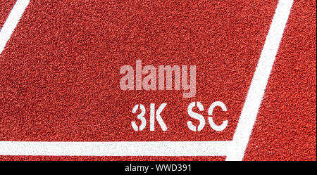 The three thousand meter start line is marked on a red track as 3K SC painted in white. - Stock Photo