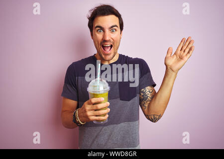 Young handsome man with tattoo drinking smoothie standing over isolated pink background very happy and excited, winner expression celebrating victory Stock Photo