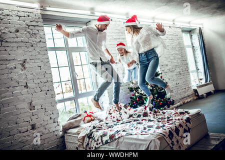 Family spending X-mas time at home. Happy family jumping on bed together. - Stock Photo