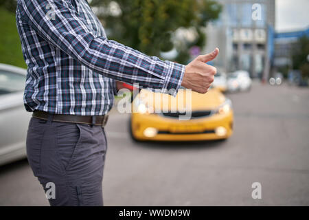 Picture of man with outstretched hand stopping taxi in afternoon on blurred background of modern city - Stock Photo