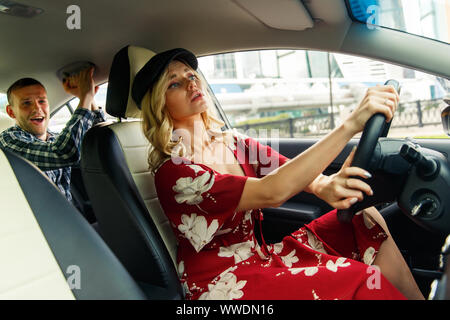 Photo of woman driver driving and male passenger riding in car during day - Stock Photo