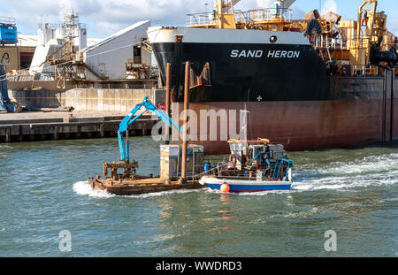Port of Poole, southern England, UK.   A deck cargo vessel  underway and working in Poole Harbour, UK. Passing the Sand Heron a larger vessel. - Stock Photo