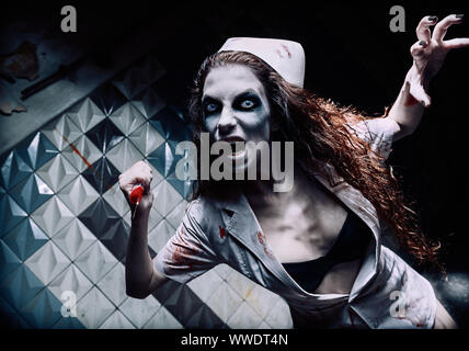 Horror shot: the terrible evil crazy nurse (doctor) attacking by bloody syringe. Zombie woman (living dead). Monster from nightmare - Stock Photo