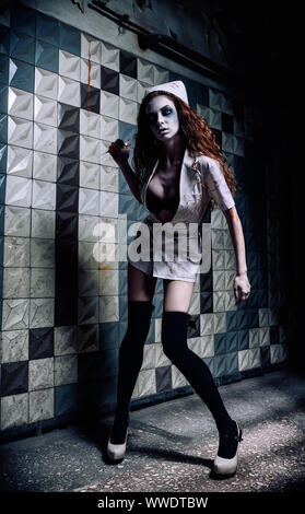 Horror shot: the grim wicked insane nurse (doctor) in bloody uniform, with syringe in hand. Zombie woman (living dead) - Stock Photo