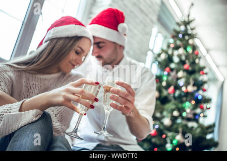 New Year. Christmas. Love. Young couple is drinking champagne, looking at each other and smiling near the Xmas tree at home - Stock Photo