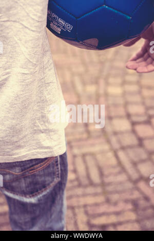 Detail of a teenage boy holding a blue football under his arm - Stock Photo
