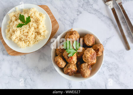 Pork meatballs in tomato sauce served with couscous - Stock Photo