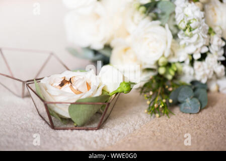 Two wedding rings in beautiful box and bouquet of flowers. Themes of engagement, declaration of love, wedding day, florist services. - Stock Photo