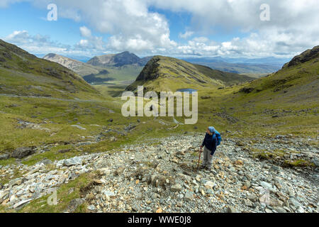 Female mountain walker high on scree slope on Blaven above Fionna Choire in the Cuillin mountains, Isle of Skye, Scotland, UK - Stock Photo