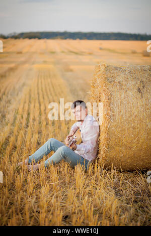 young guy is relaxing in the countryside with a guitar. Plays the guitar . Resting lying on the hay - Stock Photo
