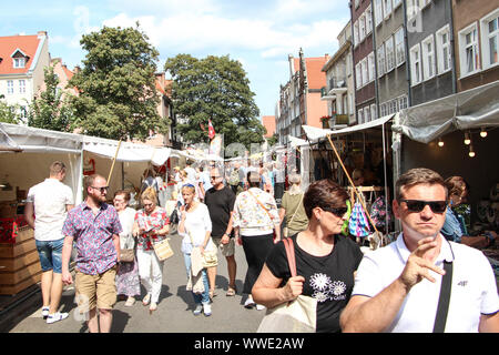 People looking for goods on on stalls and stands on the Old Town streets during 759th edition of St. Dominic's fair are seen in Gdansk, Poland on 15 August 2019 More than 1000 traders, artists and collectors participate in the Fair occupying with their stands several streets in the centre of the in the historical city centre. St. Dominics Fair is the largest open-air trade and cultural event in Poland and one of the largest such events in Europe © Michal Fludra / Alamy Live News - Stock Photo