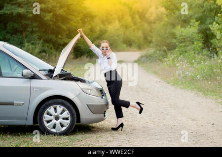 Young woman by the roadside after her car has broken down She opened the hood to see the damage - Stock Photo