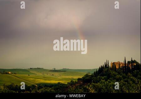 Rainbow with famous Cypress trees in the heart of the Tuscany, near Pienza, Italy - Stock Photo