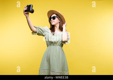 Happy traveler woman posing making selfie using camera isolated at yellow studio background - Stock Photo