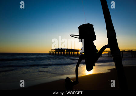 Silhouette of a reel at sunset on a beach, backlight, beautiful blue sky - Stock Photo
