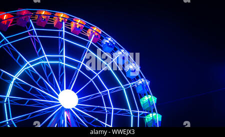 Unfocused on purpose with motion blur moving colorful Ferris wheel against the night sky at the Christmas fair in Madrid, Spain - Stock Photo