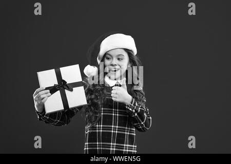 New year party. Santa claus kid. Christmas shopping. Present for Xmas. Childhood. Little girl child in santa red hat. Happy winter holidays. Small girl. presenting product. - Stock Photo