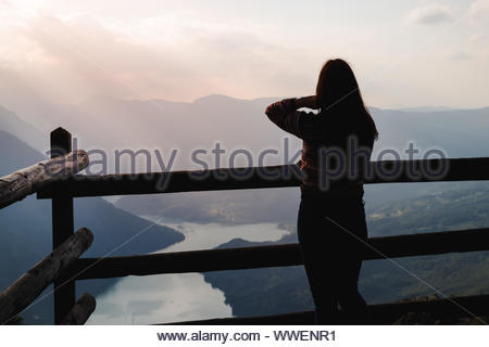 Silhouette of a young woman standing on amazing spot at mountain Tara, Serbia