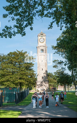 Group of young people walking in front of the Cocker Clock Tower on a sunny day in Stanley Park Blackpool Lancashire England UK. - Stock Photo