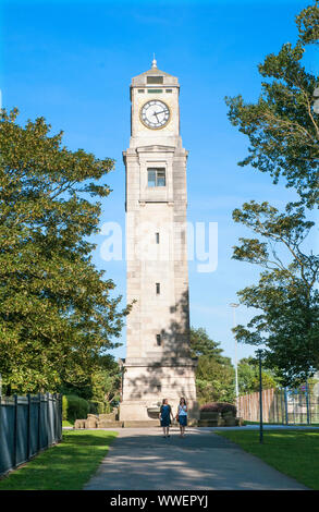 Two ladies walking in front of the Cocker Clock Tower on a sunny day in Stanley Park Blackpool Lancashire England UK. - Stock Photo