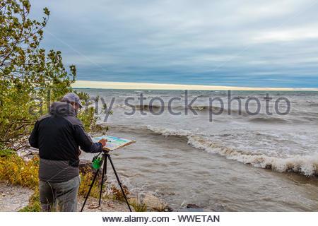 Artist painting en plein air outdoors Lake Ontario in Toronto Ontario Canada - Stock Photo