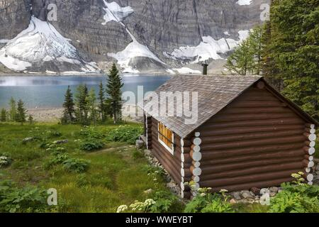 Heritage Landmark Log Cabin on a Green Alpine Meadow near Floe Lake on a great Summertime Hiking Trail in Kootenay National Park Canadian Rockies - Stock Photo