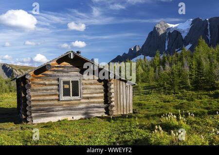 Heritage Landmark Log Cabin on a Green Alpine Meadow near Wolverine Pass below Rockwall Mountain Peak, Kootenay National Park Canadian Rockies - Stock Photo