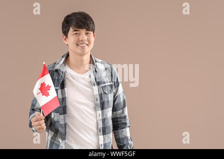 Young Asian student with Canadian flag on color background - Stock Photo