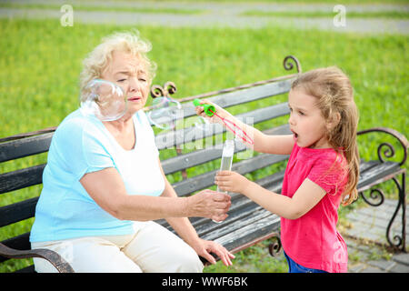 Cute little girl with grandmother blowing soap bubbles in park - Stock Photo