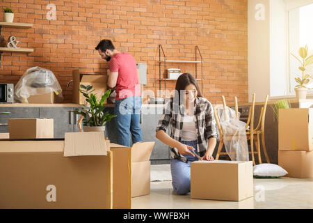 Young couple unpacking things after moving into new house - Stock Photo