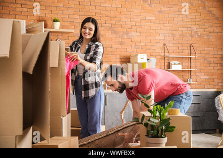 Young couple packing things before moving into new house - Stock Photo